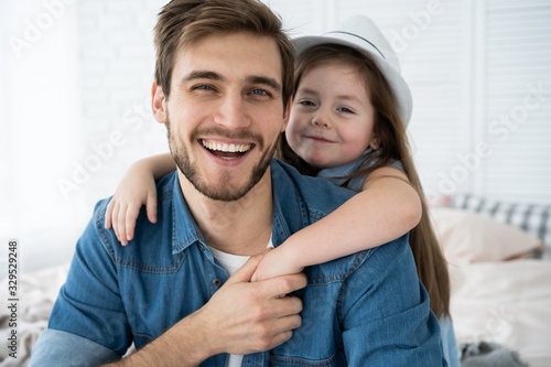 Portrait of handsome father and his cute daughter hugging, looking at camera and smiling while sitting on sofa at home.