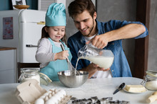 Daddy With Daughter Baking Cake Together In Home Kitchen.
