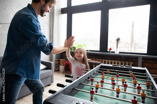 Fotografiet father and daughter playing table football at home
