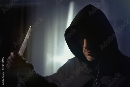 A man with a bloody knife standing in apartment, hands leather gloves, armed rob Fototapeta
