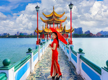 Beautiful Asian Chinese Woman Wearing Cheongsam Traditional Red Dress Standing On Bridge At Wuliting Pavilion,Kaohsiung,Taiwan.