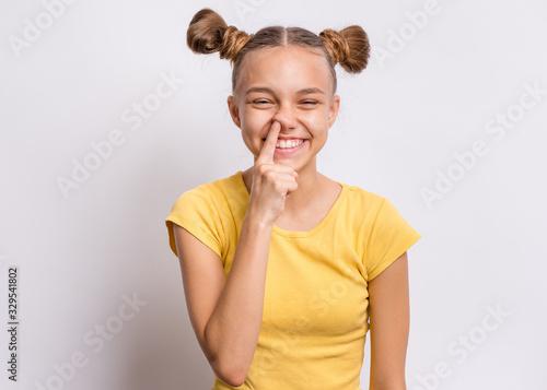 Fotografia Portrait of teen girl pick her nose on grey background