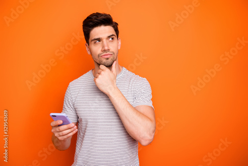 Obraz Photo of minded serious millennial guy hold telephone deep think new instagram blog post text arm on chin look side wear striped t-shirt isolated bright orange color background - fototapety do salonu