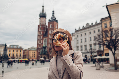 Fototapeta Tourist woman holding bagel obwarzanek traditional polish cuisine snack on Market square in Krakow. Travel Europe obraz