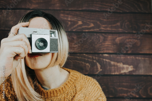 Young woman taking photographies with an analog camera Wallpaper Mural