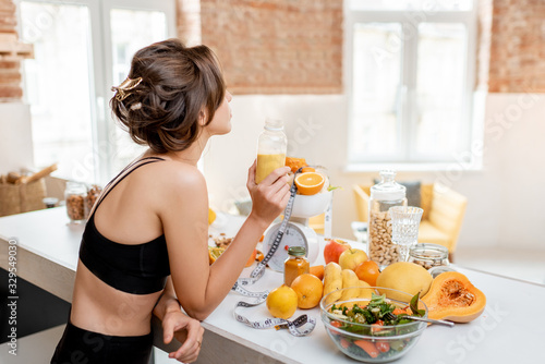 Portrait of an athletic woman having a break, drinking juice while standing with lots of healthy fresh food on the kitchen. Concept of losing weight, sports and healthy eating
