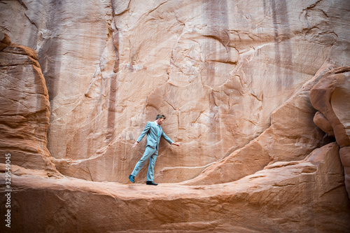 Nervous businessman taking a tentative step on a narrow ledge in a red rock cany Canvas Print