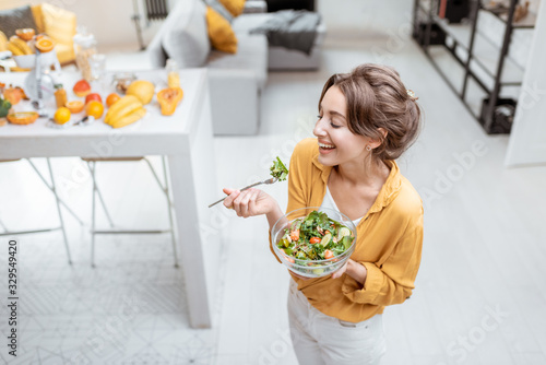 Fototapeta Portrait of a young and cheerful woman dressed in bright shirt eating salad at home. Concept of wellbeing, healthy food and homeliness obraz