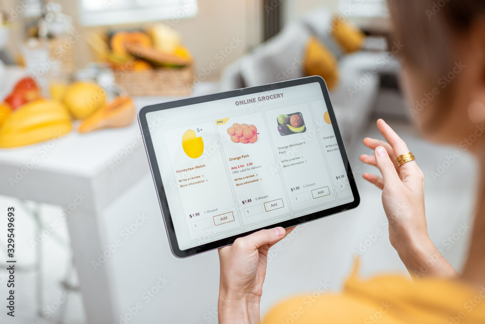 Fototapeta Woman shopping food online using a digital tablet at the kitchen, close-up view on a tablet screen. Concept of buying online using mobile devices