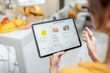 Woman Shopping Food Online Using A Digital Tablet At The Kitchen, Close-up View On A Tablet Screen. Concept Of Buying Online Using Mobile Devices
