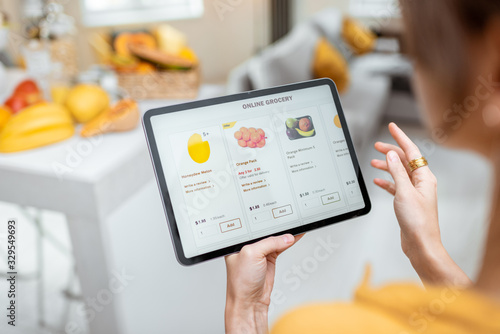 Fotomural Woman shopping food online using a digital tablet at the kitchen, close-up view on a tablet screen