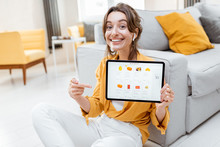 Young And Cheerful Woman Showing A Digital Tablet Screen With Launched Online Store, Shopping Online At Home. Concept Of Buying Online Using Mobile Devices