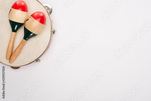 Obraz na płótnie Top view of wooden maracas on tambourine on white