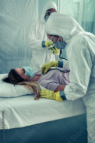 Doctors with bacteriological protection suits attending a patient Canvas Print