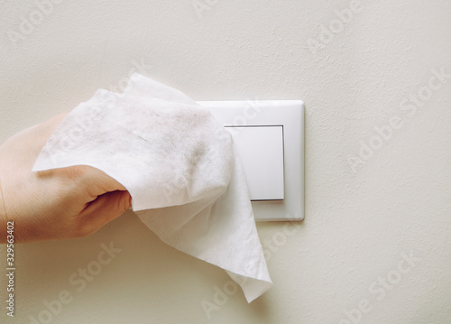 Obraz Close up view of woman hand using antibacterial wet wipe for disinfecting home room electric switch on wall. - fototapety do salonu