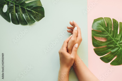Pastel manicure on a blue and pink background with palm leaves. Tropical background with woman's hands