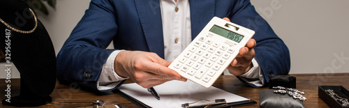 Cropped view of jewelry appraiser showing calculator near clipboard and jewelry Canvas Print
