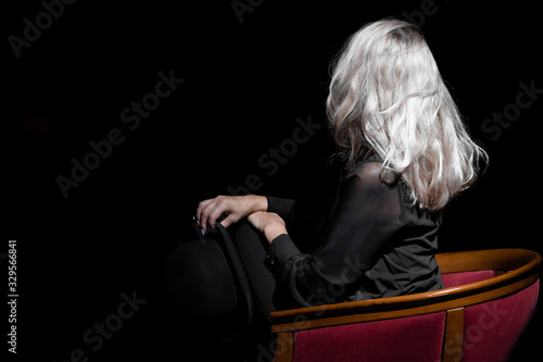 Photo Beautiful blonde Caucasian girl in black coat on a chair at the theater stage