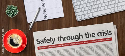 Fototapeta Newspaper on a desk -  Safely though the crisis obraz