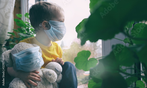 Obraz Quarantine, threat of coronavirus, virus protection, pandemic. Child and his teddy bear both in protective medical masks sits on windowsill inside house and looks out window. Focus on toy. - fototapety do salonu