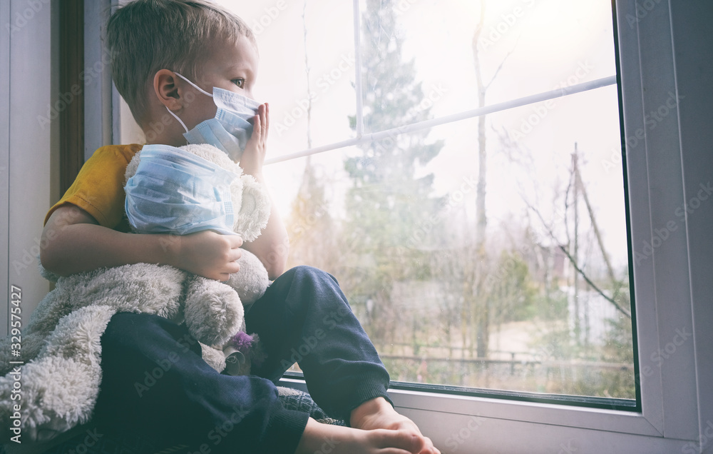 Fototapeta Illness child on home quarantine. Boy and his teddy bear both in protective medical masks sits on windowsill and looks out window. Virus protection, coronavirus pandemic, prevention epidemic.