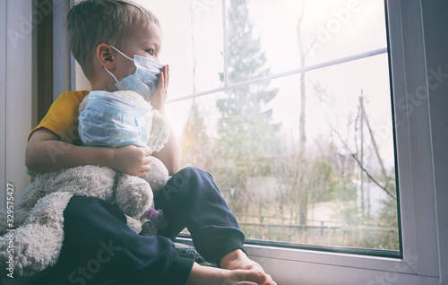 Illness child on home quarantine. Boy and his teddy bear both in protective medical masks sits on windowsill and looks out window. Virus protection, coronavirus pandemic, prevention epidemic.