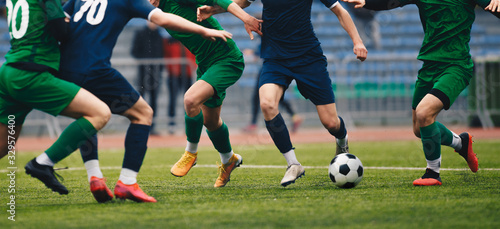 Obraz Soccer football player dribbling a ball and kick a ball during match in the stadium. Footballers in action on the tournament game. Adult football competition - fototapety do salonu