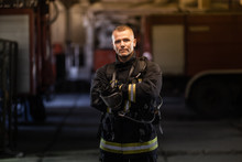 Firefighter Portrait Wearing Full Equipment And Emergency Rescue Equipment. Taking Off Oxygen Mask All Sweaty After Successful Intervention. Fire Trucks In The Background.
