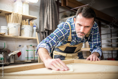 Photo Professional carpenter polishing wood using abrasive paper in carpentry workshop