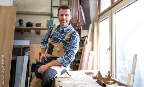 Obraz Portrait of mature carpenter posing in his carpentry workshop with tools in background - fototapety do salonu
