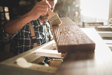 Craftsman Painting A Wooden Bo...