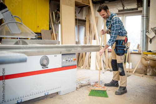 Craftsman cleans his carpentry workshop after work Canvas Print