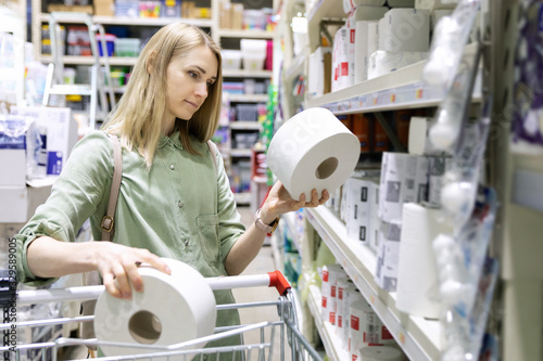 Fotomural woman buy toilet paper rolls at household goods store