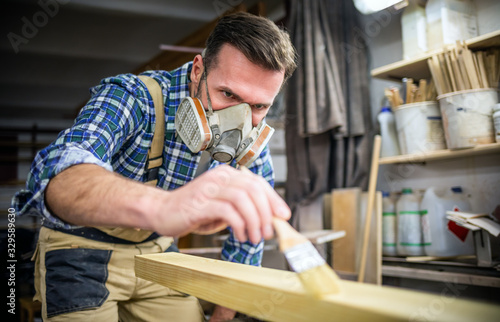 Carpenter with mask applies paint using paintbrush in carpentry workshop Canvas Print