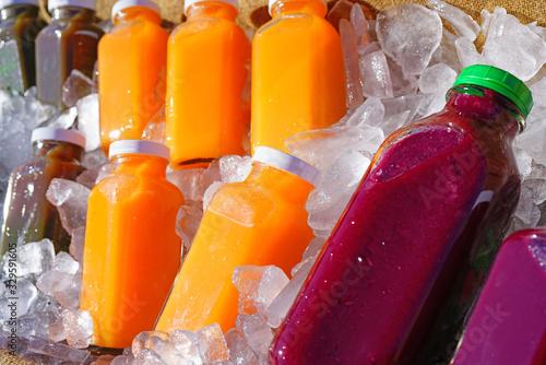 Fototapeta Bottles of colorful cold pressed juice on ice