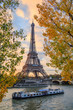 Peniche passing in front of the Eiffel tower in Paris France on an autumn day surrounded by brown leaves of trees, tour Eiffel in the fall