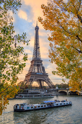 Peniche passing in front of the Eiffel tower in Paris France on an autumn day surrounded by brown leaves of trees, tour Eiffel in the fall - 329592417
