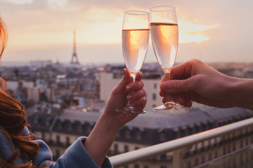 couple drinking champagne or wine in Paris luxurious restaurant with view of Eiffel tower, luxury romantic getaway honeymoon
