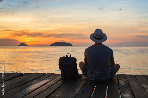 Foto wanderlust travel, tourist with backpack sitting near the sea, man enjoying suns