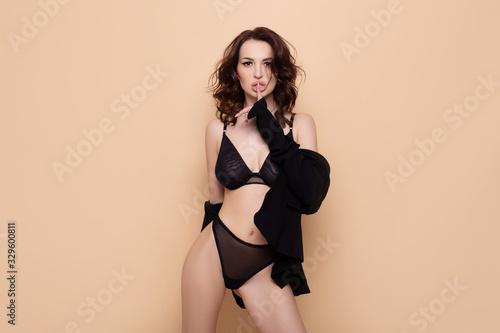 Fototapeta Sexy brunette model girl posing in black lingerie over beige background obraz