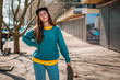 Leinwanddruck Bild - A young Caucasian hipster woman poses with a skateboard. In the background, an alley. Close up. Concept of sports lifestyle and street culture