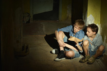 Sad Boys Sitting On Floor In A Dark Cellar
