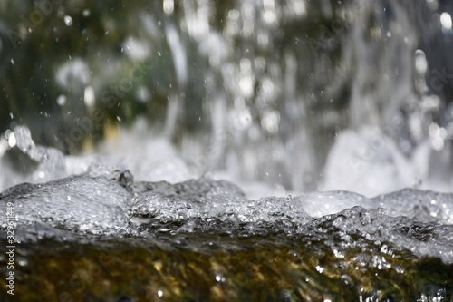 Frozen water drops of forest waterfall
