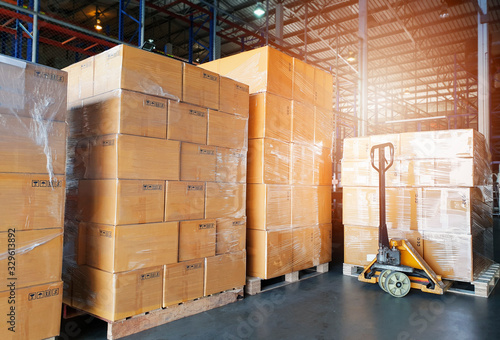 Fototapeta Interior of warehouse, stack package boxes on pallets and hand pallet truck, warehouse industry delivery shipment goods, logistics, transport obraz