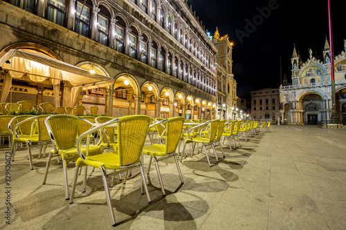 Night view of one Bar on the Piazza San Marco showing a multitude of empty chairs and empty square
