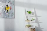 Art near books and plants on bookshelf near white wall with sunlight