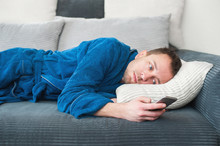 A Man Lies On The Couch, Bored And Looks At The Phone