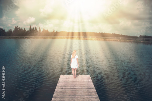 Fotografía Magical sunlight with beams with a woman standing on wooden pier.