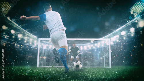 Fotografía Soccer scene at night match with player in a white and blue uniform kicking the