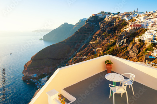 Fototapeta Beautiful sunset at Santorini island, Greece. Two chairs with table on the terrace with sea view. Famous travel destination obraz